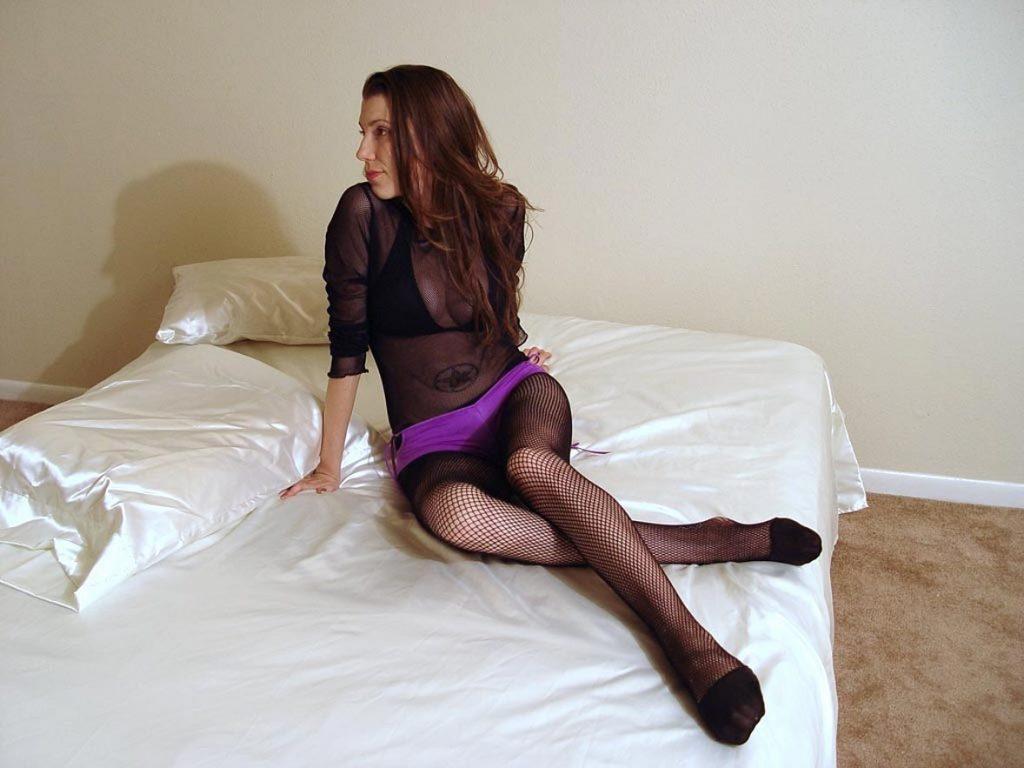 Hübsche junge Frau sitzt auf dem Bett